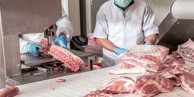 Arbeiter in der Fleischindustrie zerlegen Fleischstücke