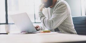 Mann mit Schreibtisch am Laptop